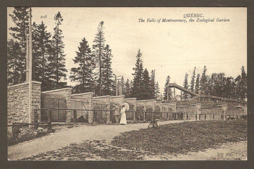Carte postale Neurdein ND 208: Québec - Les Chutes de Montmorency, une Cage du Jardin Zoologique. Un couple chic de visiteurs, devant un alignement de cages, au zoo Holt Renfrew. En arrière-plan, on peut voir la structure de la glissoire d'hiver.