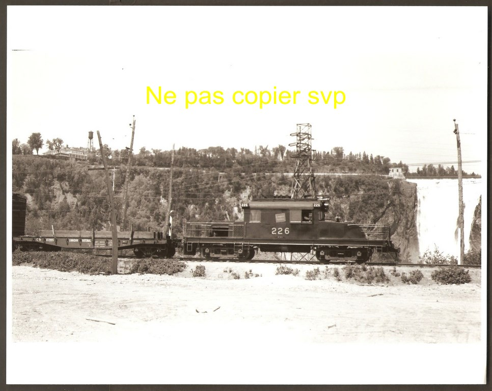 Train de maintenance du Canadien National, devant la chute Montmorency. On peut voir également l'hôtel Kent House, en haut à gauche. Par ailleurs, détail à remarquer: la citerne se trouvant alors derrière le bâtiment. La photographie est datée de juin 1953.