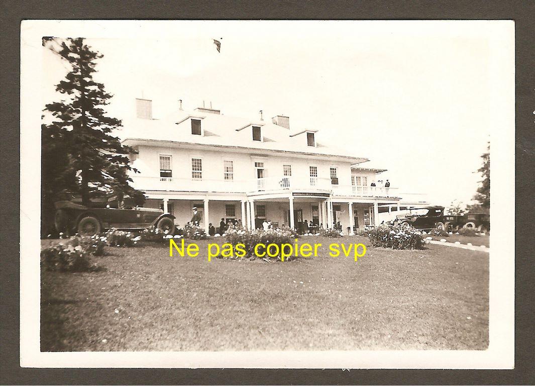 Photo de petites dimensions (8,9 x 6,2 cm) illustrant l'hôtel Kent House, au cours des années 1920. On remarque une automobile d'époque stationnée devant l'établissement, ainsi que quelques autres, plus en retrait, à droite.