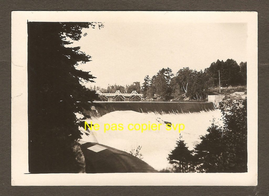 Tirage photographique de 1920 environ, montrant l'arête du barrage traversant la rivière Montmorency, juste avant le dénivelé de la chute. De plus, à l'arrière-plan, on remarque l'ancien pont qui enjambait alors la rivière. Au premier plan, à gauche, passe le conduit amenant l'eau de la station de pompage à la centrale hydro-électrique se trouvant en bas de la falaise, à l'ouest de la chute.