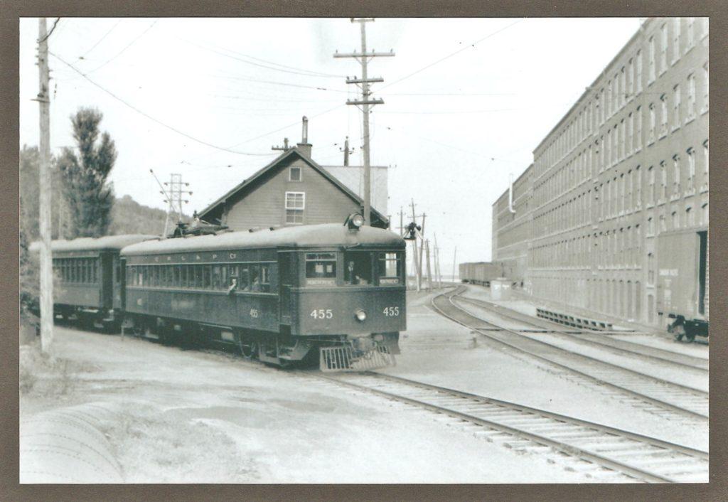 Le tramway 455 de la Quebec Railway Light & Power Company, devant la gare de la chute Montmorency et derrière l'usine de la Dominion Textile.