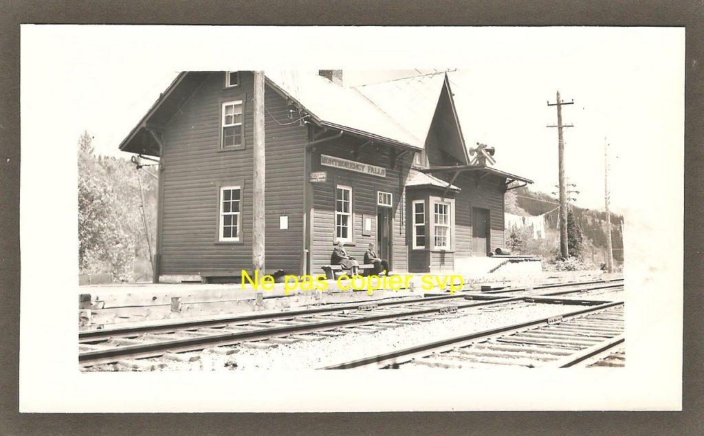 Deux personnes assises sur un banc devant la gare de la chute Montmorency autour des années 1940.