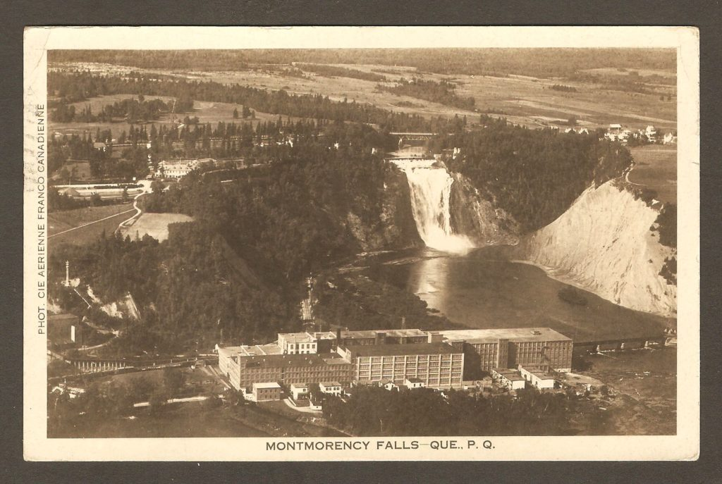 Photo aérienne de la Dominion Textile, avec la chute Montmorency en arrière plan, sur une carte postale datant des années 1930.