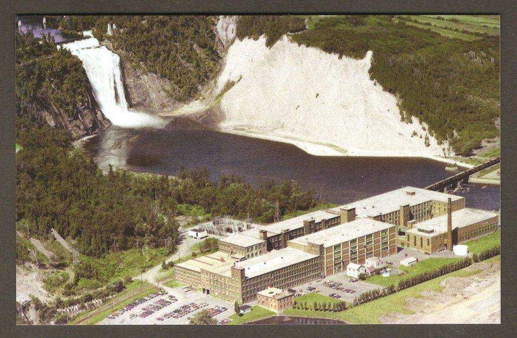 Carte postale de la belle collection des Archives du Photographe, publiée en 2010, et illustrée d'une photo aérienne de Charles-Henri Leclerc, prise le 2 août 1976. On y voit les bâtiments de la Dominion Textile, ainsi que la chute Montmorency, en arrière-plan.