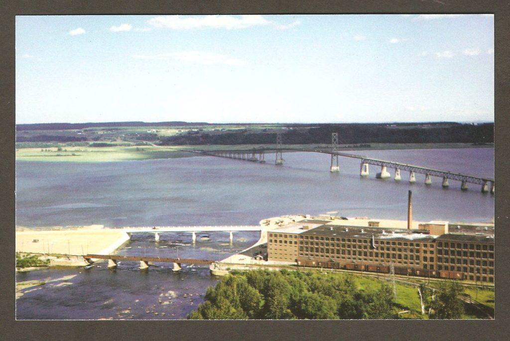Chute Montmorency : carte postale de la collection des Archives du Photographe, illustrée elle aussi d'une photo de la Dominion Textile, prise du haut de la falaise. En arrière-plan, on peut voir le pont et l'île d'Orléans.