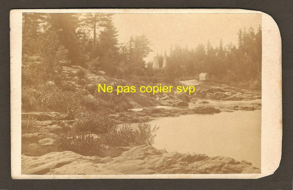 Carte de visite montrant la rivière Montmorency, juste avant la chute. On y aperçoit, en arrière-plan, les piliers de la rive ouest du pont qui s'est effondré en 1856. Par ailleurs, la rivière est asséchée au moment de la prise de la photo. On remplissait peut-être alors le bassin de la centrale électrique construite un peu plus en amont, sur la rivière.