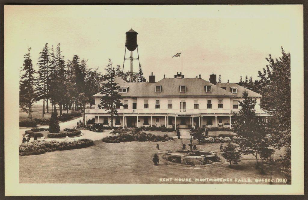 Une carte postale « photo réelle » montrant la façade du Kent House, vers 1925. Des automobiles d'époque sont stationnées devant l'hôtel et on remarque la présence de personnes sur le balcon donnant sur la salle de bal, à droite.