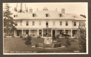 Cette carte postale de S. J. Hayward, publiée autour de 1920-1930, montre la façade du Kent House. On remarque notamment une auto de l'époque, les colonnes inclinées soutenant la citerne derrière l'hôtel, ainsi que la fontaine, devant celui-ci.