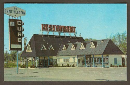 Le restaurant La Dame Blanche sur une carte postale plus récente, datant vraisemblablement des années 1960. On remarque d'important changements : la tourelle est disparue et une imposante affiche « restaurant » a été installée sur le toit. Par ailleurs, un panneau-réclame portant l'inscription « curb » est apparue. L'âge du service à l'auto était arrivé...