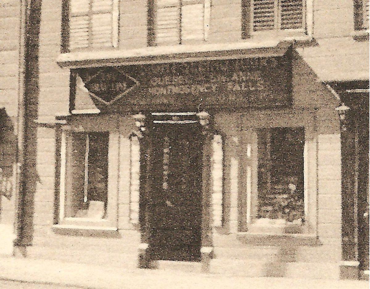 Une carte postale montrant des façades d'immeubles commerciaux, sur la rue Saint-Louis, en face du Château Frontenac. On remarque notamment que le panneau publicitaire au-dessus de la porte centrale fait la promotion de tours en direction de « Ste Anne & Montmorency Falls ». Et qu'il s'agit d'un bureau de la Q.R.L.&P. stratégiquement situé pour attirer les touristes.