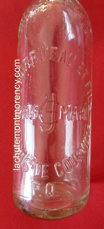 Bouteille d'eau gazeuse datant de 1910 environ et portant l'inscription embossée « J. L. CORRIVEAU ET FILS / TRADE MARK / ST. LOUIS DE COURVILLE / P.Q. ». Ce petit fabriquant d'eau gazeuse était auparavant situé à Montmorency.