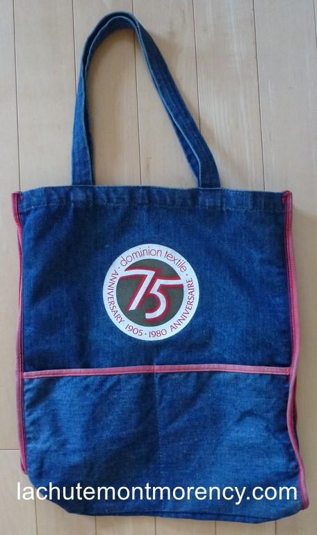 Un sac souvenir en denim, distribué en 1980 afin de souligner le 75e anniversaire de la Dominion Textile (1905-1980).