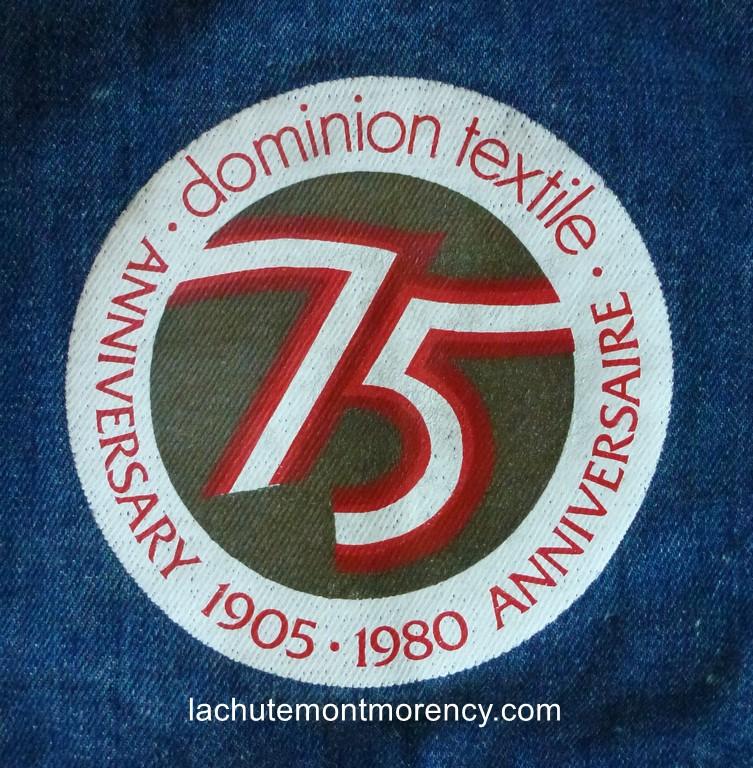 Un sac souvenir en denim, distribué en 1980 afin de souligner le 75e anniversaire de la Dominion Textile. Inscription sur le sac.