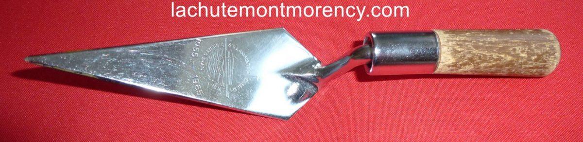 Une truelle miniature promotionnelle destinée à souligner le 10e anniversaire de l'ouverture de l'usine des Ciments du St-Laurent, qui se trouvait à la limite ouest de Montmorency, à la jonction de la ville de Villeneuve.